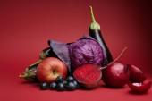 """Постер, картина, фотообои """"крупным планом вид органических спелое яблоко, виноград, лук, свекла, капуста и баклажаны на красном"""""""
