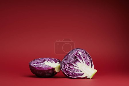 Photo for Fresh ripe organic sliced purple cabbage on red background - Royalty Free Image