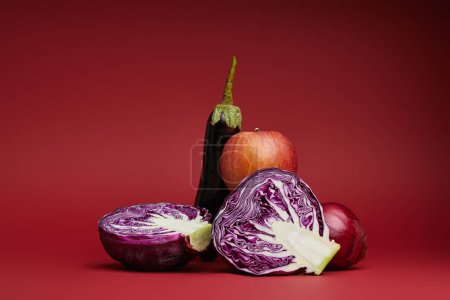 fresh ripe apple, eggplant, onion and sliced cabbage on red background