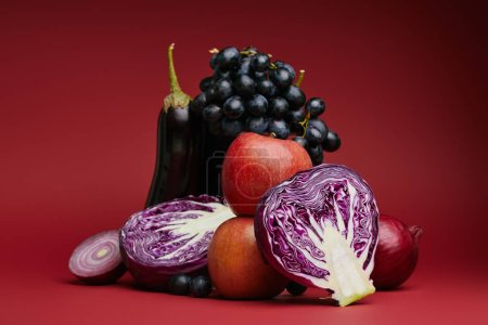 close-up view of apples, grapes, eggplant, cabbage and onions on red