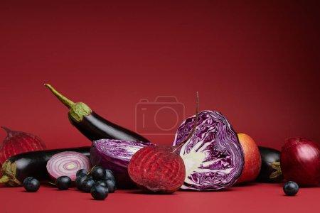 vue rapprochée des fruits et légumes biologiques mûrs sur fond rouge