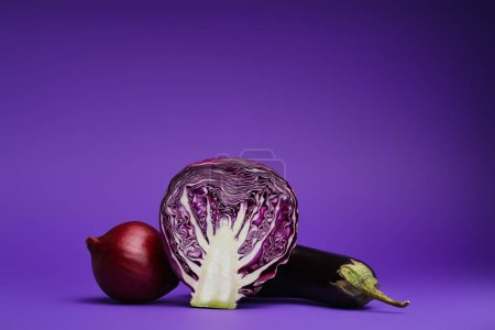close-up view of sliced cabbage, onion and eggplant on purple background