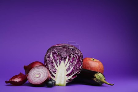 close-up view of sliced cabbage, onions, grapes, eggplant and apple on purple