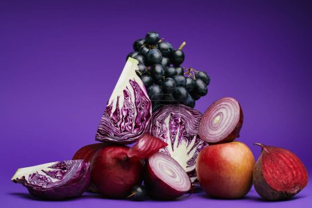 close-up view of grapes, apple, beetroot, onions and sliced cabbage on purple