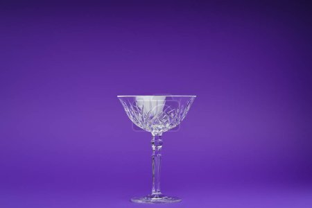close-up view of single empty glass on purple background