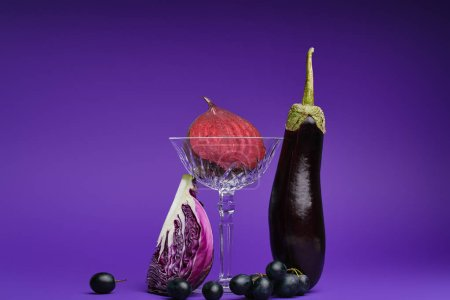 close-up view of halved beetroot in glass, sliced cabbage, grapes and eggplant on purple
