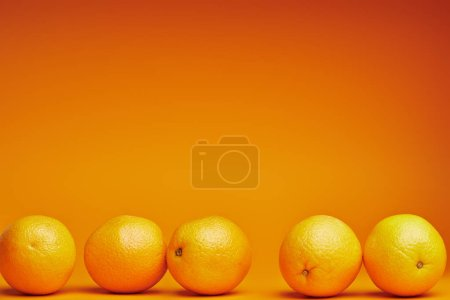 close-up view of fresh ripe oranges on orange background