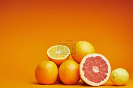 Photo for Close-up view of fresh ripe whole and sliced citrus fruits on orange background - Royalty Free Image