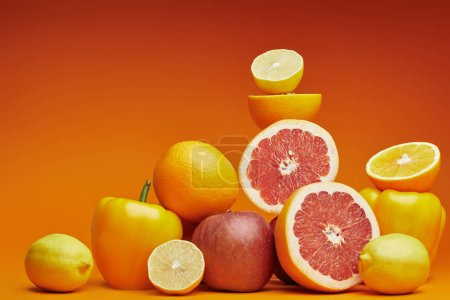 Photo for Fresh ripe organic citrus fruits, apples and bell peppers on orange background - Royalty Free Image