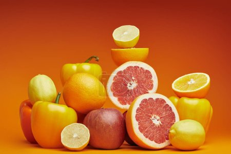 fresh ripe citrus fruits and bell peppers on orange background