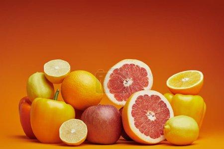 Photo pour Vue rapprochée des agrumes mûrs frais et poivrons sur fond orange - image libre de droit