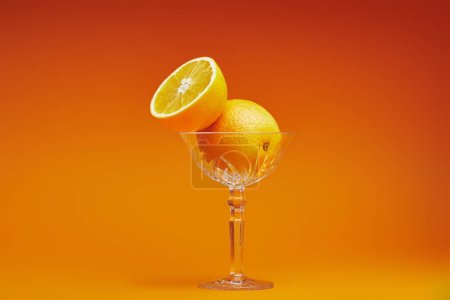 close-up view of fresh ripe oranges in glass on orange background