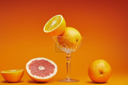 close-up view of fresh ripe oranges in glass and sliced grapefruit on orange