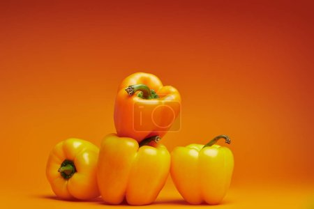 Photo for Close-up view of fresh organic bell peppers on orange - Royalty Free Image