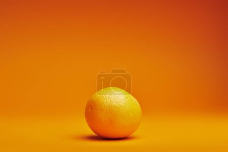 close-up view of fresh ripe whole orange on orange background