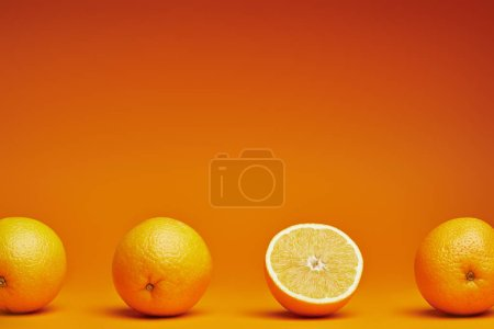 close-up view of fresh ripe whole and halved oranges on orange background