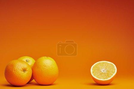 Photo pour Vue rapprochée d'oranges entières et coupées en deux sur fond orange - image libre de droit