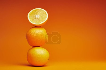 Photo for Close-up view of whole and sliced oranges on orange background - Royalty Free Image