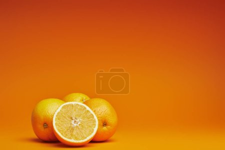 Photo for Close-up view of fresh ripe whole and sliced oranges on orange background - Royalty Free Image