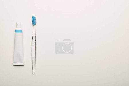 top view of toothbrush and toothpaste arranged on white backdrop, dentistry concept