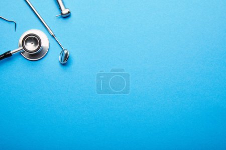 flat lay with arranged stainless dental instruments on blue tabletop, dentistry and dental care concept