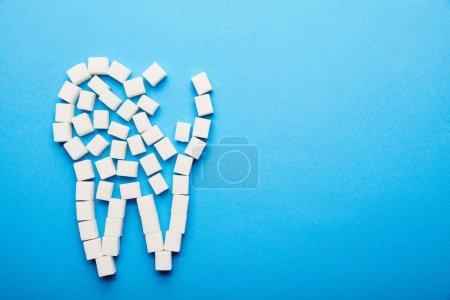Photo pour Vue de dessus des cubes de sucre blanc disposées en dents signe sur fond bleu, concept de soins dentaire - image libre de droit