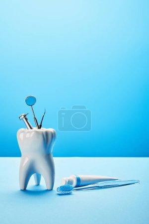 Photo pour Vue rapprochée du modèle de dent blanche, de la brosse à dents, du dentifrice et des instruments dentaires en acier inoxydable sur fond bleu - image libre de droit