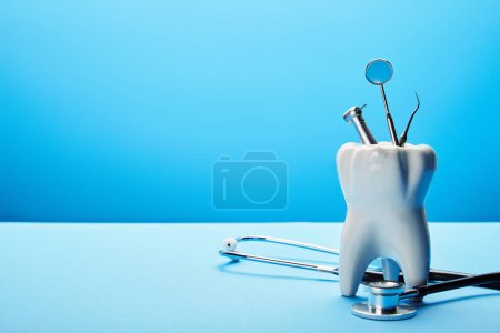 close up view of white tooth model, stethoscope and stainless dental instruments on blue backdrop