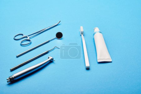 close up view of arrangement of sterile dental instruments, stethoscope, toothbrush and toothpaste on blue backdrop, dental care concept