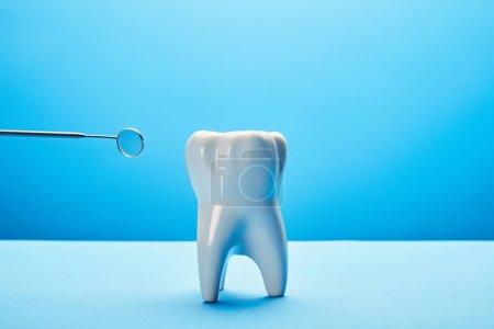 Photo pour Vue rapprochée du modèle de dent et du miroir buccal sur fond bleu - image libre de droit