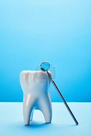 close up view of tooth model and dental mouth mirror on blue backdrop