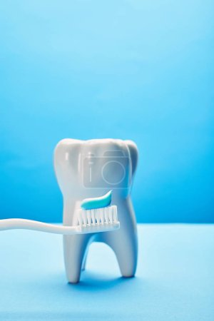close up view of tooth model and toothbrush with paste on blue background, dental care concept