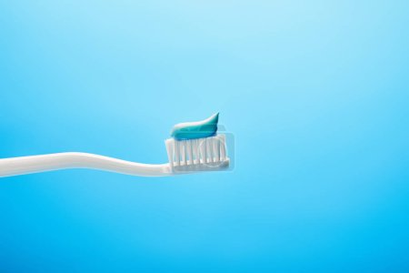 close up view of toothbrush with paste on blue backdrop