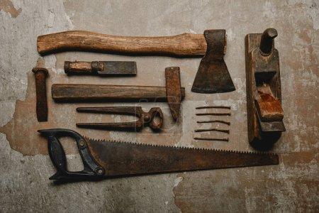 Vista superior de varias herramientas de carpintería oxidadas sobre fondo viejo