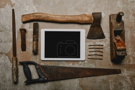 Flat lay with different carpentry tools and digital tablet on old surface