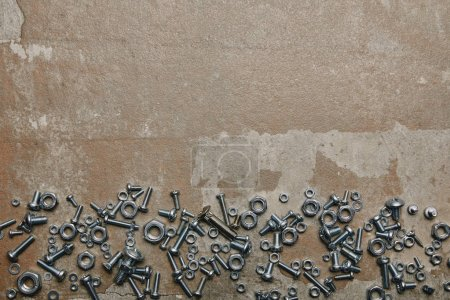 Photo for Top view of screws and bolts arranged on the background of old  surface - Royalty Free Image