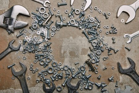 Top view of screws, bolts and wrenches arranged on the background of old  surface