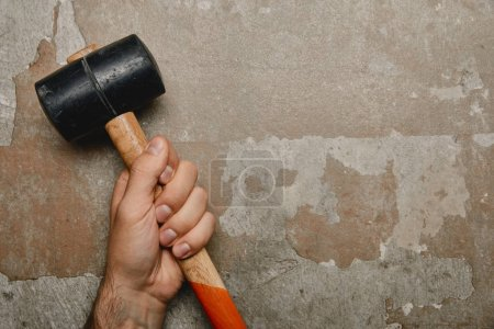Photo for Partial view of man holding mallet on old background - Royalty Free Image