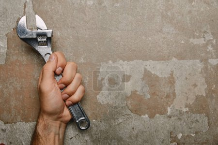 Partial view of man holding monkey wrench on old surface