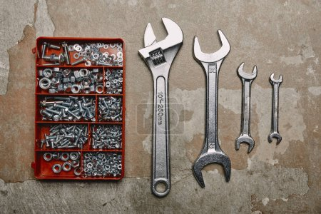 Flat lay with Set of wrenches tools and box of screws on the background of old  surface