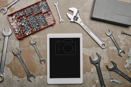 Flat lay with digital tablet and different carpentry tools on the background of old  surface