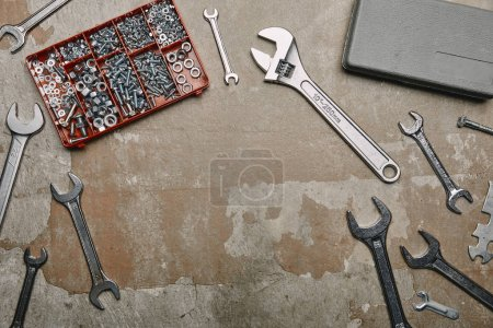 Top view of set of carpentry tools and box with screws on old surface