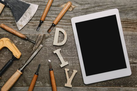 Flat lay with digital tablet, diy sign and different carpentry tools on wooden background