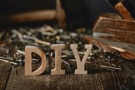 Close up of diy sign on dark wooden table on the background of nails and logs