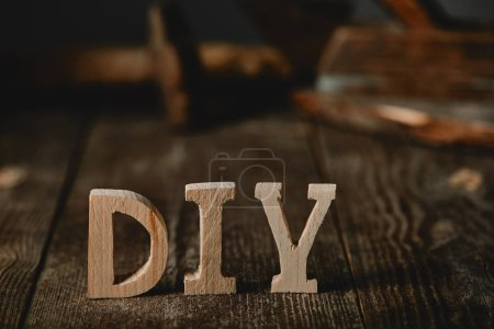 Close up of diy sign on dark wooden table on the background of logs