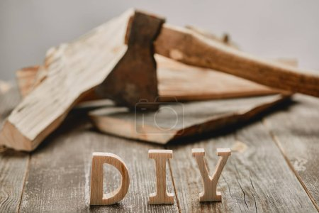 Close up of diy sign on wooden table on the background of logs and axe