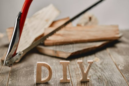 Close up of diy sign on wooden table on the background of logs and hacksaw