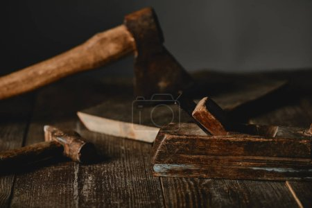 Close up view of axe, hammers and wood logs on wooden table on grey background