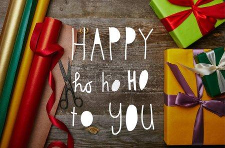 """Foto de Vista del arreglo de envolver papeles, regalos de Navidad con cintas y tijeras en tablero de madera con superior """"feliz ho ho ho te"""" inspiración - Imagen libre de derechos"""