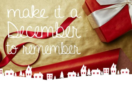 "top view of christmas gift and ribbon on red and golden wrapping papers background with ""make it a December to remember"" inspiration"